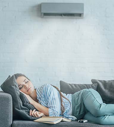 woman sleeping on couch and air conditioner running